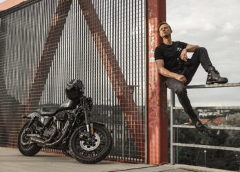 Biker wearing motorcyclist jeans and posing with his bike