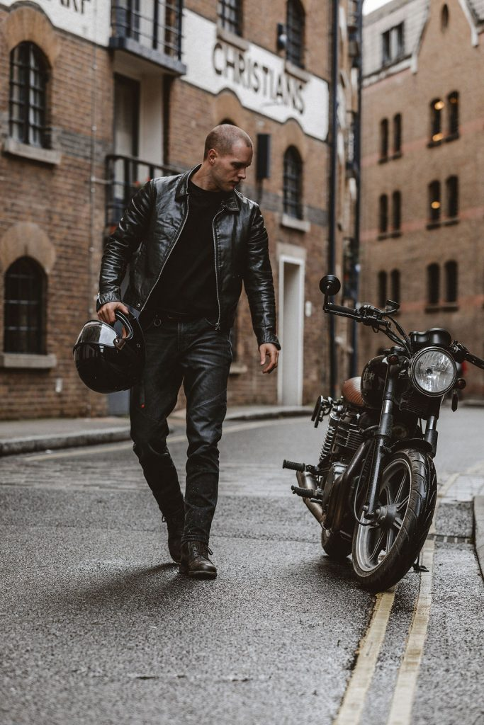 Cafe Racer in front of his bike with the helmet